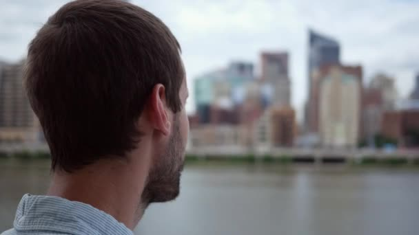 Filler shot of a man looking sideways with a city in the background