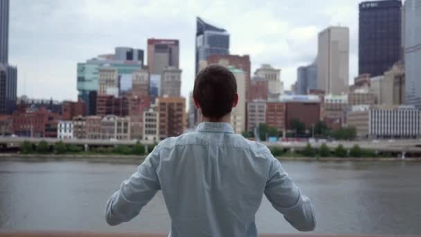 A man lifts his arms in a celebratory victory stance against cinematic skyline