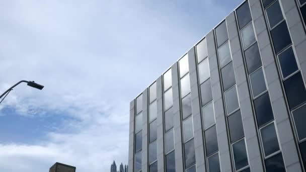 Eine äußere Einspielung eines Chrom grauen Bürogebäudes am Sommertag