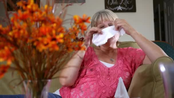 A Caucasian woman has allergies and sneezes in her home