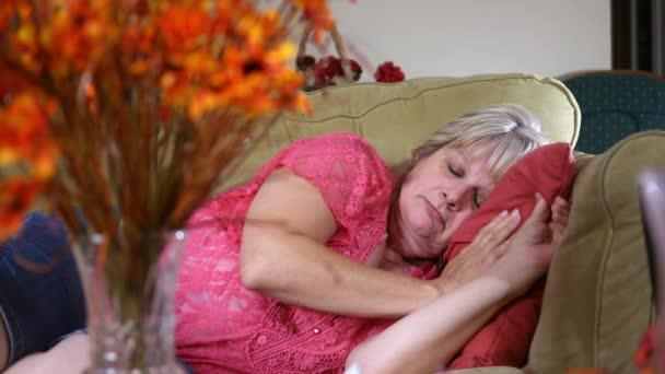 Kavkazský žena pokojně spí na gauči