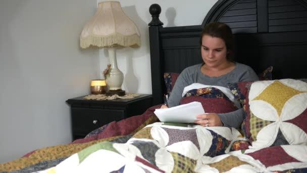 caucasian teacher grading papers her bed night class failing stock