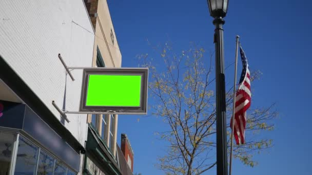 A Green Screen sign outside of a store with american flag blowing - replace content shot