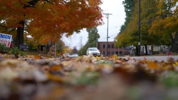 Low angle of traffic driving down street in Pennsylvania neighborhood on peaceful autumn afternoon
