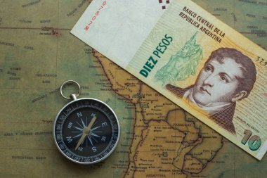 old map of south america with argentine money and compass, close-up