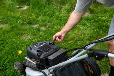 Starting an lawn mower to mow lawns.