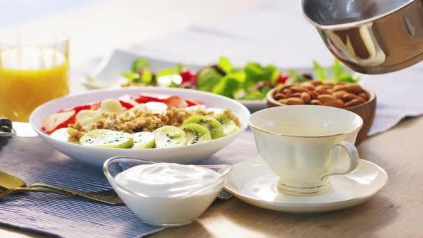 Turecká káva nalévá horkou vodu. Zdravá snídaně z müsli granola čerstvé ovoce kiwi jahody jougurt a džus. Zpomalený záběr videa na černošky Magic Cinema kamery 6k na Raw formátu.
