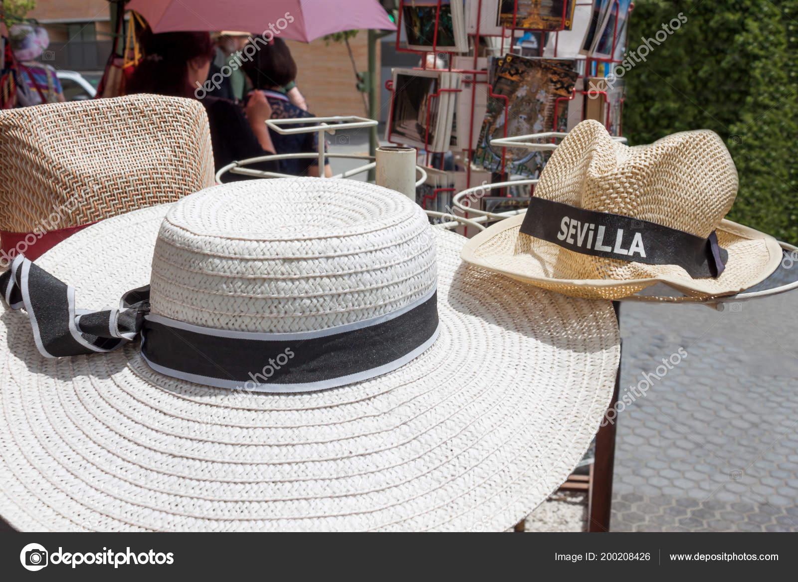 Slámy dámský klobouk se stuhou a klobouk Slaměný panák s nápisem Sevilla.  Letní zboží pro turisty ve Španělsku v turistickém– stock obrázky 1d4731ac2e