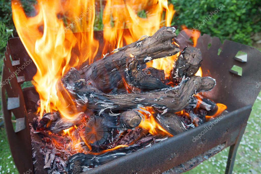 Empty charcoal grill with open fire, burning branches of grapes, coals, outdoor summer concept