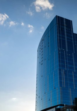 Modern building of glass and concrete against the blue sky with clouds.