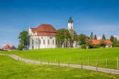 Fotografie Schöne Aussicht auf die berühmte ovale Rokoko-Wallfahrtskirche Wies (Wieskirche), seit 1983 UNESCO-Weltkulturerbe, mit grünen Wiesen an einem sonnigen Tag mit blauem Himmel und Wolken in Bayern, Deutschland