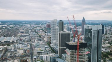 aerial view of cityscape with skyscrapers and buildings near crane in Frankfurt, Germany