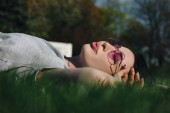 Photo beautiful young woman relaxing on grass in park