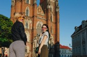 Photo two attractive smiling women standing in front of wroclaw cathedral and looking at camera