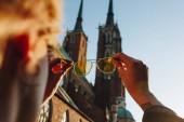 Fotografia ritagliata colpo della holding della donna eleganti occhiali da sole e guardando attraverso la Cattedrale di wroclaw