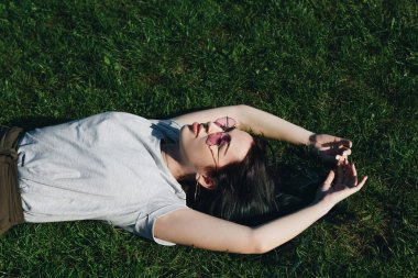 high angle view of attractive young woman relaxing on grass in park