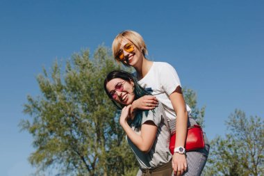 bottom view of happy young women embracing in front of blue sky