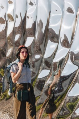 WROCLAW, POLAND - 18 MAY 2018: beautiful young woman in front of sculpture made of reflective material