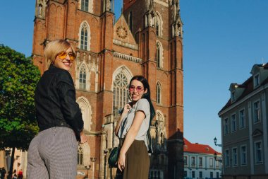 two attractive smiling women standing in front of wroclaw cathedral and looking at camera