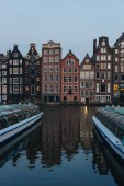20 MAY 2018 - AMSTERDAM, NETHERLANDS: facades of ancient building above canal on twilight, Amsterdam, Netherlands