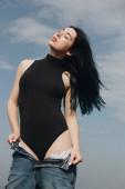 Fotografia giovane donna sensuale nel nero Body assunzione di jeans davanti al cielo nuvoloso