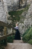 Photo beautiful girl standing on stairs with wooden railings on rocky cliff, Etretat, Normandy, France