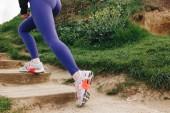 Fotografia ritagliata vista sportiva in scarpe da ginnastica che funziona sulle scale, Etretat, Francia