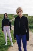 Fotografie young sportswomen posing on green cliff, Etretat, Normandy, France