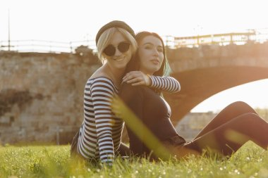 beautiful young women embracing while sitting on grass in park on sunset