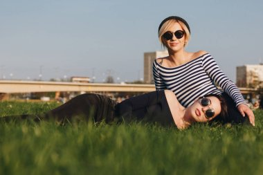 beautiful young women relaxing on green grass in park