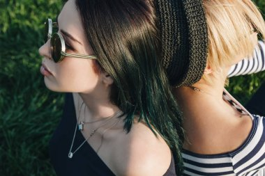 close-up shot of attractive young women sitting on green grass back to back