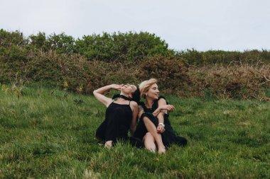 happy young women in black relaxing on green meadow