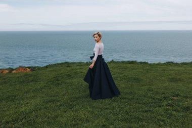 elegant young woman posing on majestic cliff, Etretat, Normandy, France