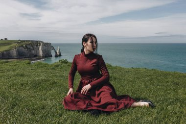 fashionable girl sitting on green cliff near the sea, Etretat, Normandy, France