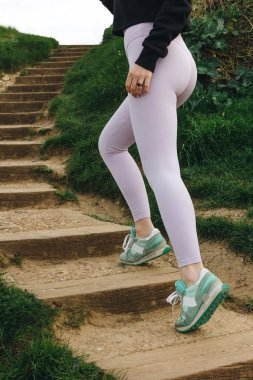 cropped view of sportswoman in stylish sportswear and sneakers, Etretat, France