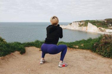 back view of sportswoman squatting on cliff near the sea, Etretat, France