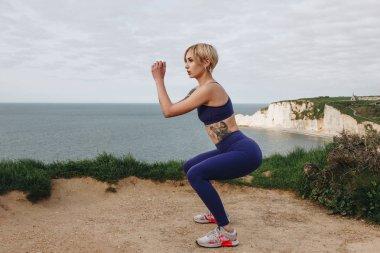 beautiful woman in sportswear squatting on cliff, Etretat, France