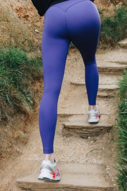 low section of sportswoman in sneakers running up on stairs, Etretat, France