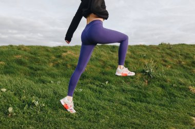 cropped view of athletic woman in stylish sportswear exercising on green grass, Etretat, France