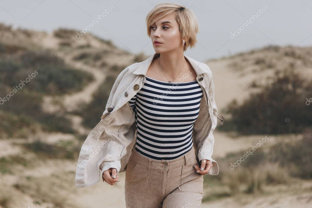 beautiful young woman in stylish striped shirt and vintage jacket walking on sand dunes