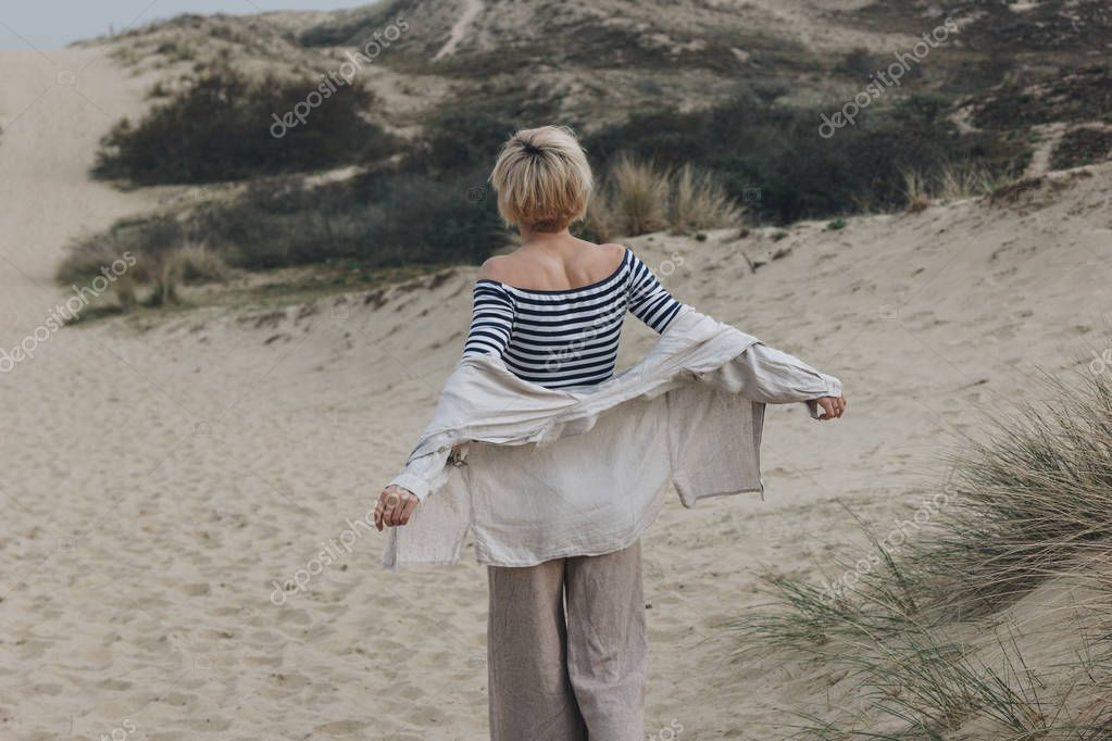 rear view of young woman in stylish clothes on sand dune