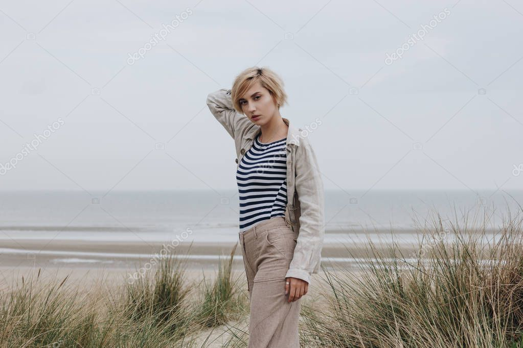 stylish young woman in striped shirt and jacket on sandy shore