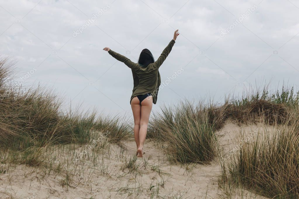 rear view of young woman on sand dune under cloudy sky