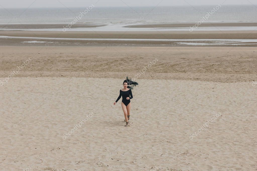 attractive young woman in black bodysuit running on sandy seashore
