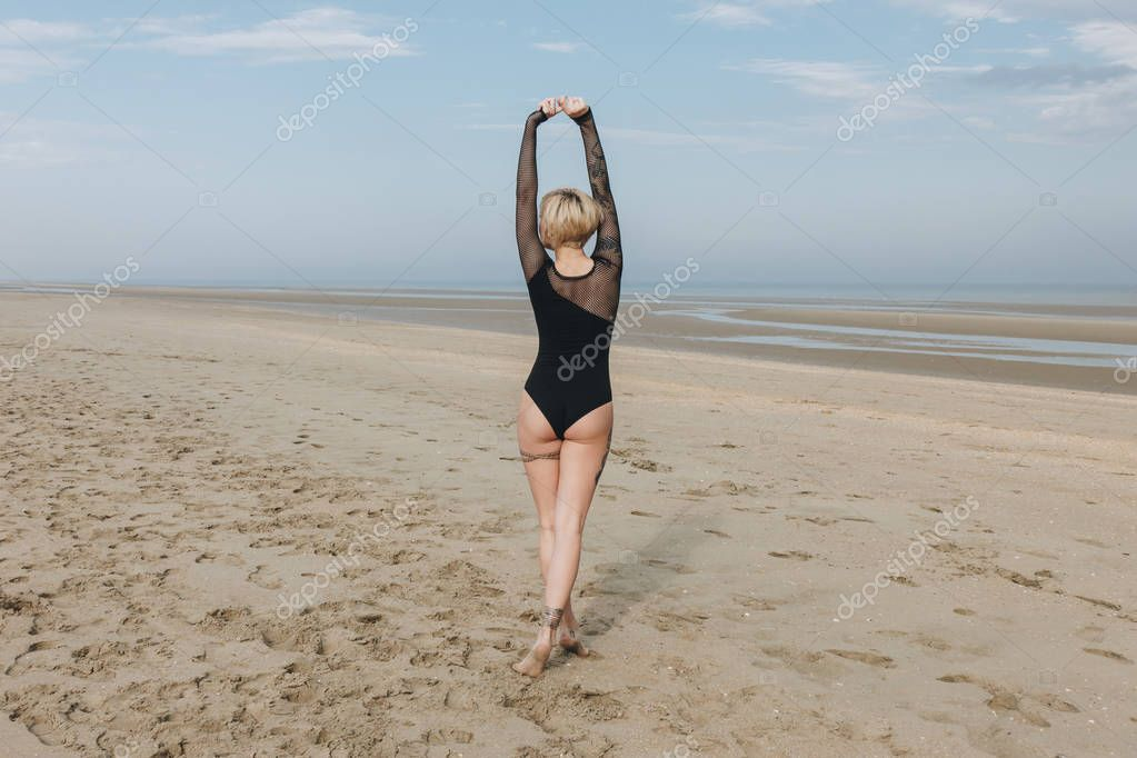 rear view of attractive young woman in black bodysuit on sandy beach
