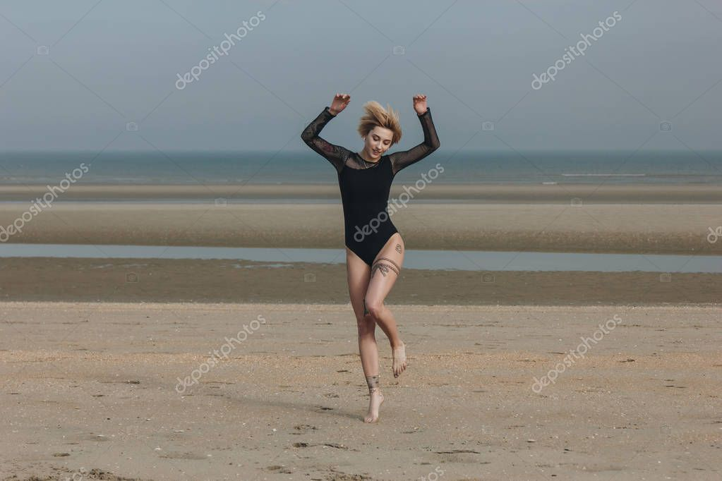 beautiful young woman in black bodysuit jumping on shore on cloudy day