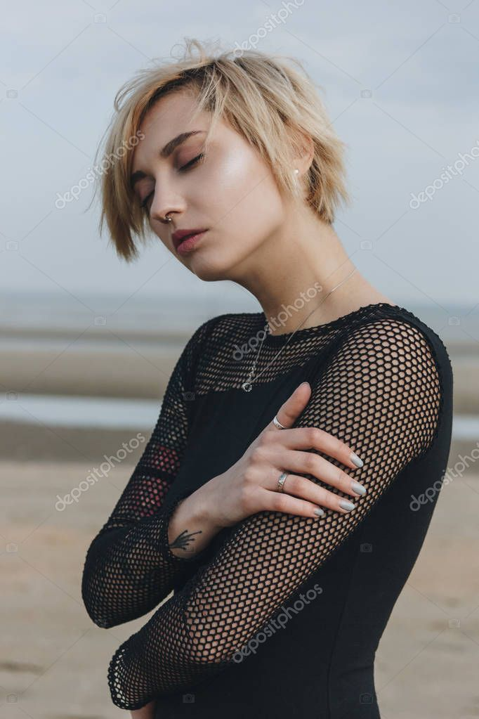 sensual young woman in black shirt in front of seashore on cloudy day