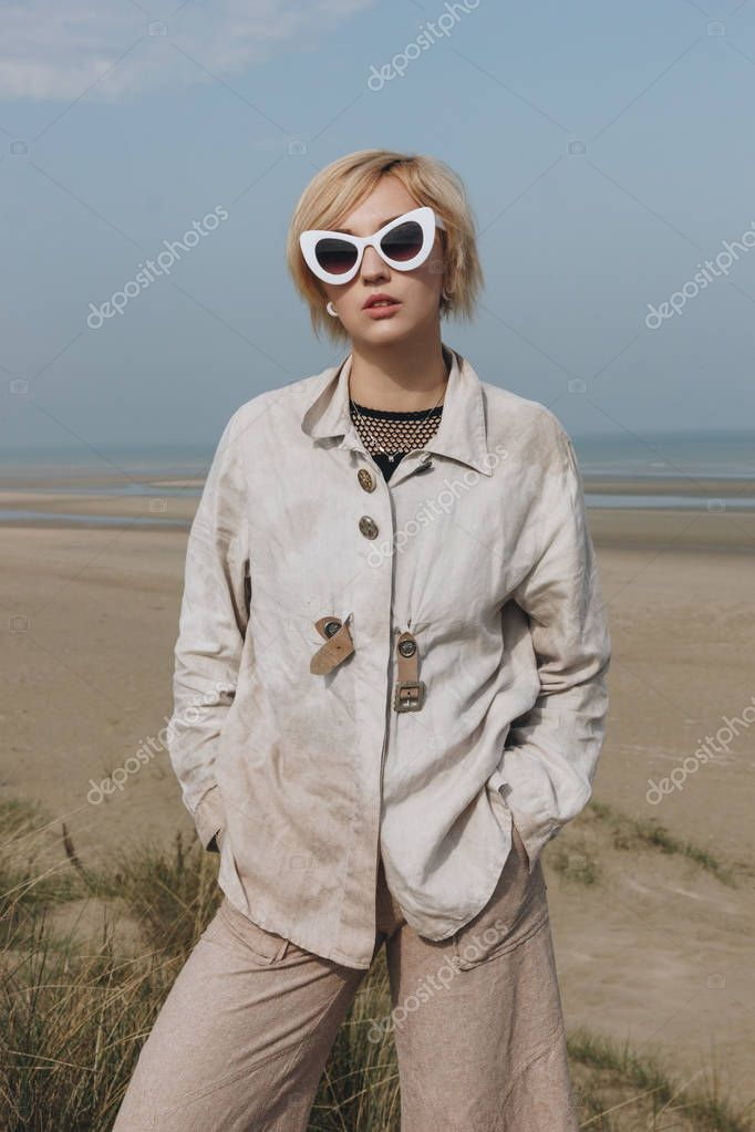 beautiful young woman in vintage fashionable clothing in front of seashore
