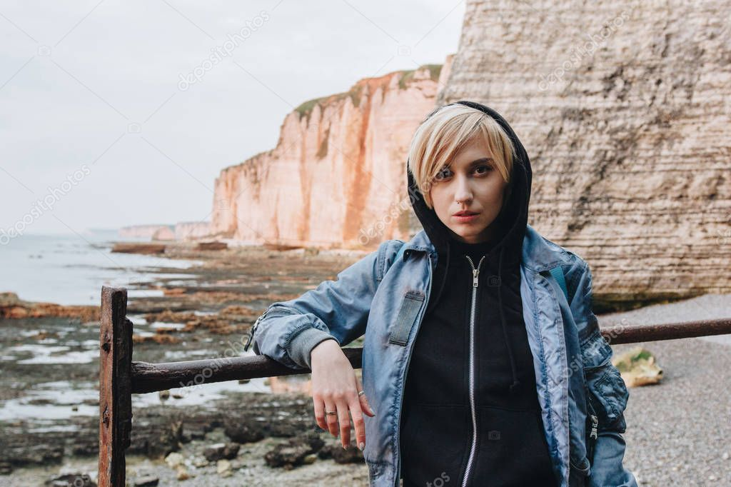 beautiful young woman standing in front of rocky cliffs on seashore