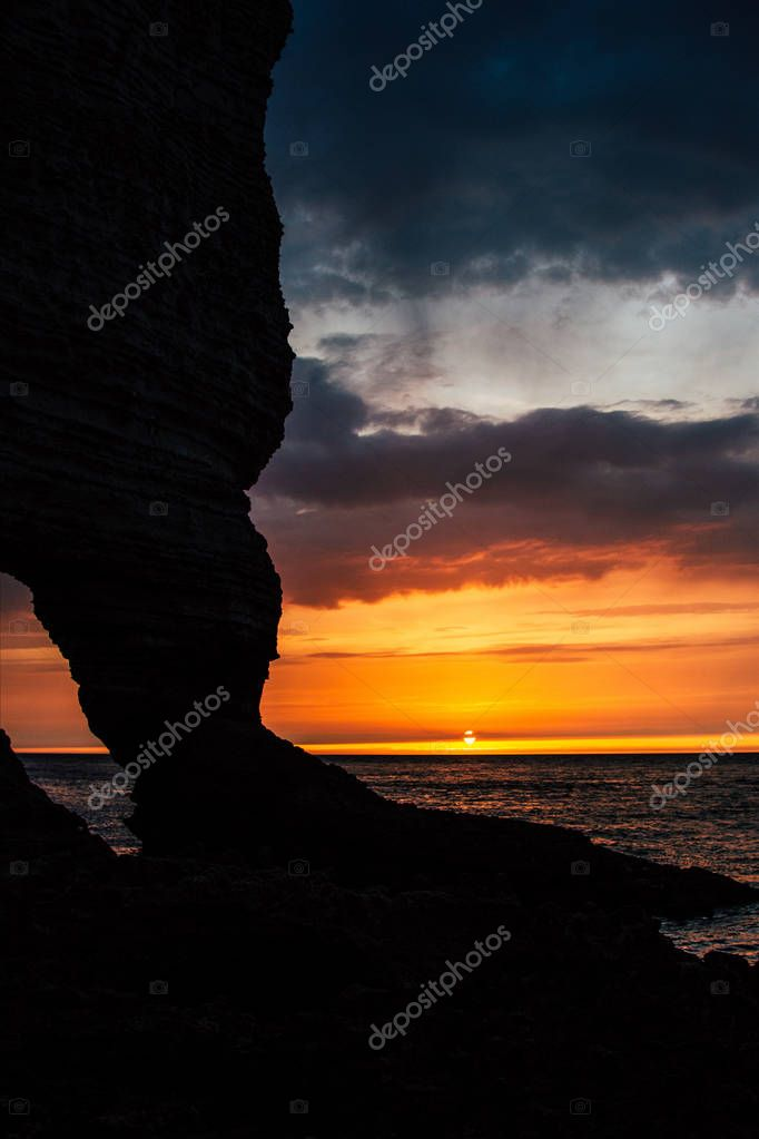 rocky cliff on cloudy sunset, Etretat, France